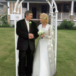 Colour photo of man and woman outside under an arch wearing wedding dress and suit