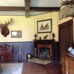 Colour photo of a room with moose head , elk head, fireplace