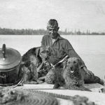 B&W photo of man with two dogs on a boat on lake