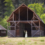 Colour photo of a man and woman walking from a large barn wearing wedding dress and suit