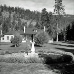 B&W photo of a heritage manor house, garden in foreground