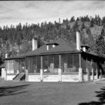B&W photo of a heritage bungalow style manor house, hill and trees in background