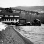 B&W photo of a building and wharf, launch boat in foreground