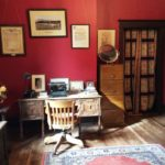 Colour photo of an antique desk and chair in a room with red walls